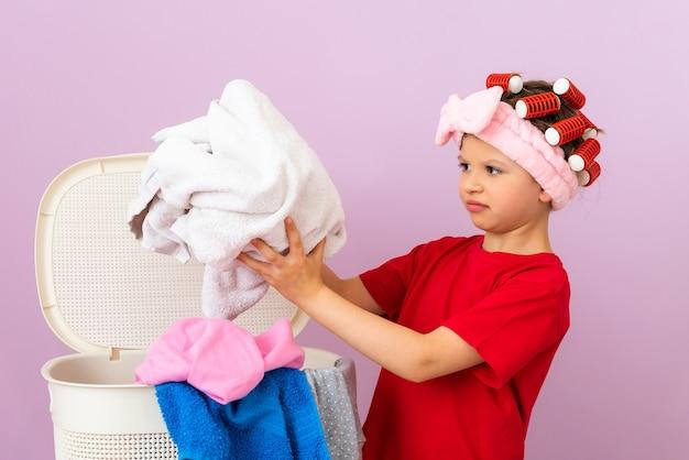 어린 소녀가 더러운 세탁물을 바구니에 넣습니다. 집 청소 및 세탁.