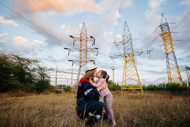 小さな女の子が母親のためにエンジニアリングワーカーにヘルメットをかぶっています。将来の世代と環境への関心。エネルギー。