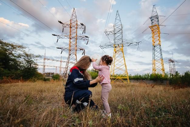 어린 소녀가 공학 노동자에게 어머니를 위해 헬멧을 쓰고 있습니다. 미래 세대와 환경에 대한 관심. 에너지.