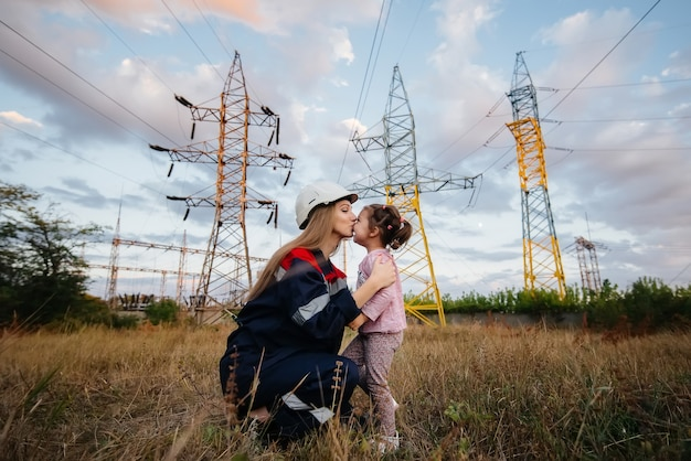 Маленькая девочка надевает каску матери инженеру