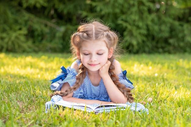 녹색 잔디밭에서 책을 읽는 어린 소녀