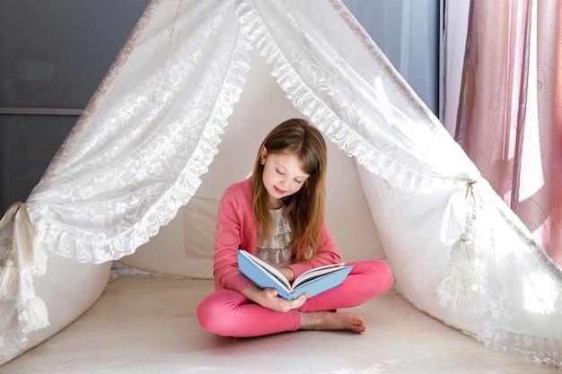 Маленькая девочка читает книгу дома, сидя на полу