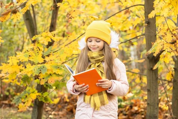 小さな女の子が秋の森の中で本を読みます。