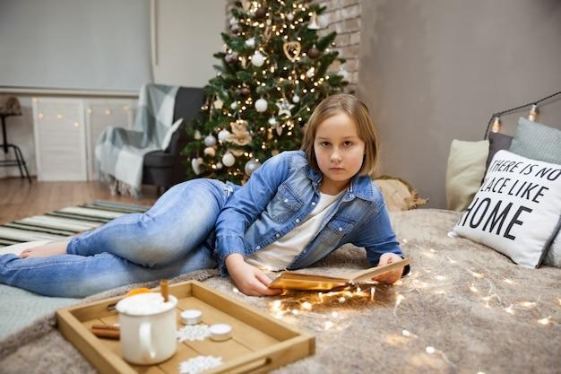 小さな女の子がお祝いのクリスマスツリー、ソフトフォーカスの中で寝室のベッドで本を読む