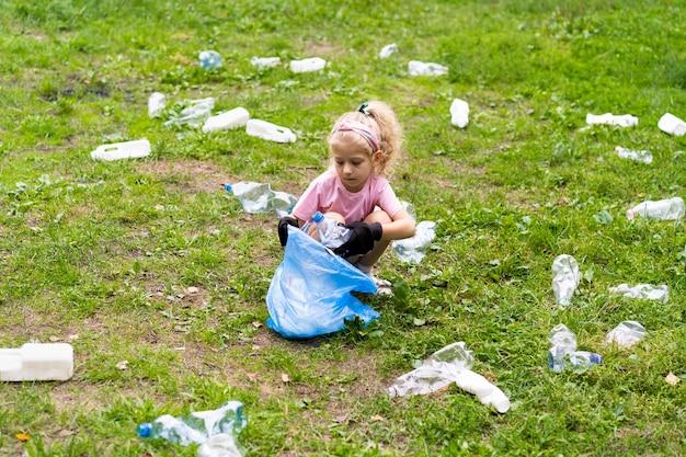 어린 소녀는 플라스틱 쓰레기를 제거하고 야외에서 생분해성 쓰레기 봉투에 넣습니다. 생태, 폐기물 처리 및 자연 보호의 개념. 환경 보호.