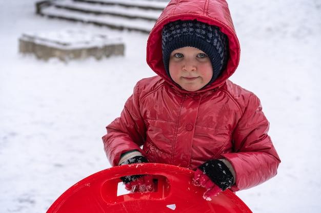 Маленькая девочка катается на санках с зимней горки. зимние каникулы.