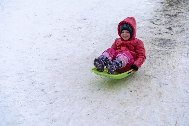 小さな女の子が冬の滑り台からそりに乗ります。冬休み。