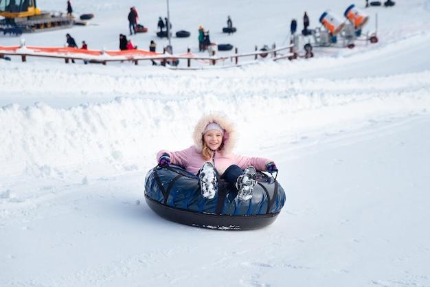 小さな女の子がスライドを下ってチュービングに乗る