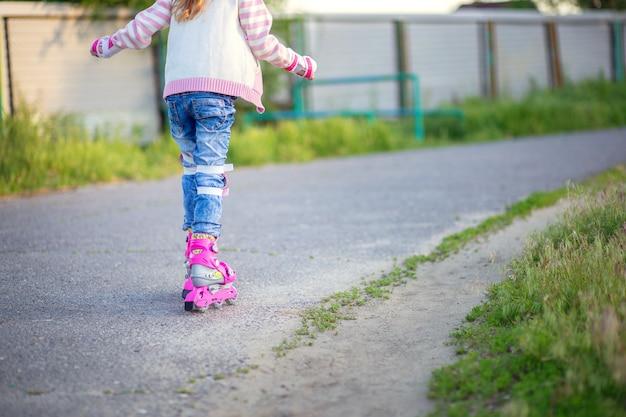 Маленькая девочка катается на розовых роликовых коньках по асфальту