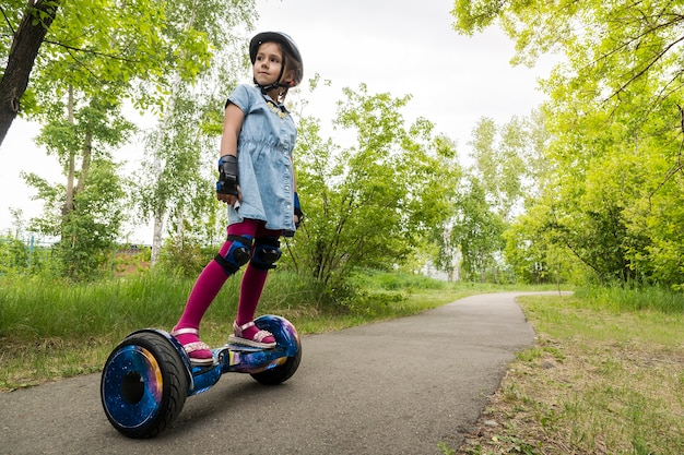 전기 자기 균형 스쿠터를 타는 어린 소녀. 아이가 자이로 스쿠터에서 균형을 잡고 있습니다. 개인 에코 운송, 자이로 스쿠터, 스마트 밸런스 휠. 대중적인 전기 운송