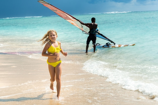 Маленькая девочка бежит по пляжу тропического острова маврикий в индийском океане.