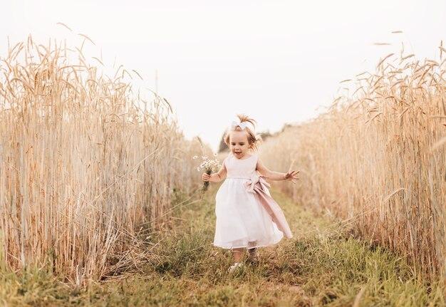 Маленькая девочка в белом платье бежит по пшеничному полю.