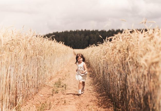 어린 소녀는 밀밭을 통해 실행됩니다. 소녀는 재미 있고 기쁨으로 웃습니다. 해질녘 옥수수의 익은 귀가 있는 들판.