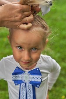 小さな女の子の髪をとかし、弓を結びます。縦ショット