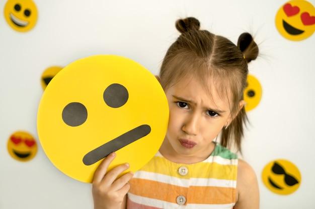 ふくれっ面で悲しい少女は、彼女の手に段ボールの悲しい絵文字を持っています