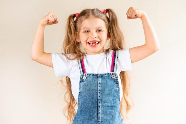 Маленькая девочка показывает свои бицепсы.