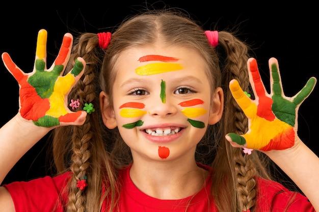 Маленькая девочка показывает руки, испачканные гуашевыми красками.