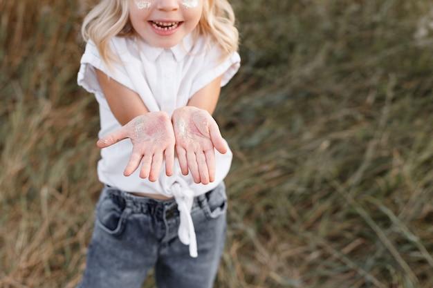 小さな女の子がスパンコールをつけた手のひらを見せます。閉じる。テキスト用の空き容量