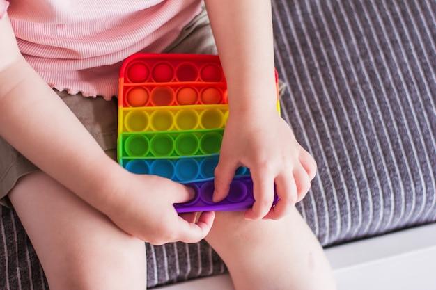 Маленькая девочка сидит и держит в руках игрушку радугу, хлопай непоседу. сенсорная игрушка push bubble fidget силиконовая игрушка для снятия стресса. игрушка-антистресс для ребенка с особыми потребностями