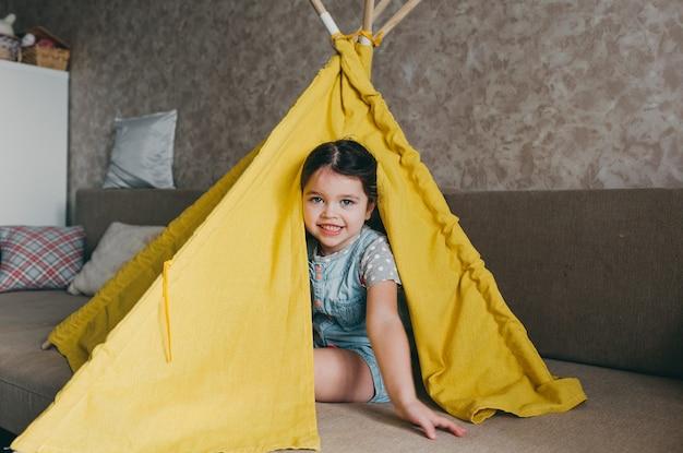 Маленькая девочка сидит и улыбается внутри желтого вигвама. домашние игры и развлечения для детей