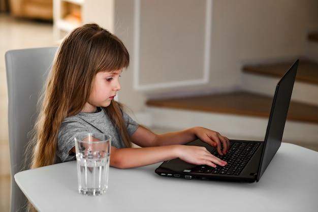 小さな女の子がテーブルに座って、コンピューターを使って遠隔で勉強します。オンラインスクール、ホームスクーリング。