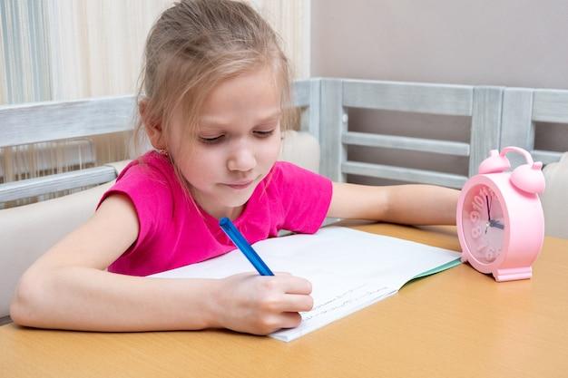 Маленькая девочка сидит за столом и записывает домашнее задание в тетрадь. время учиться. ребенок учится дома.