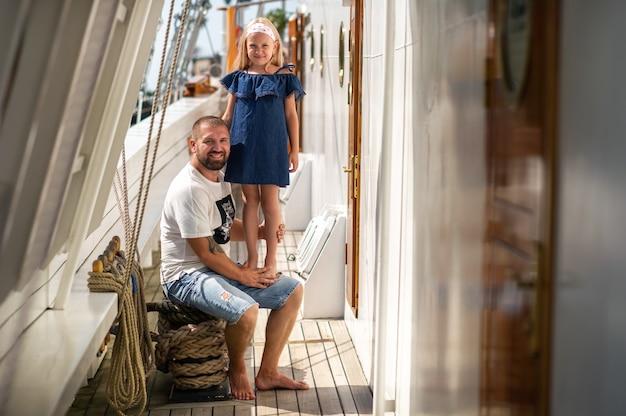 小さな女の子が父親の腕の中に座って、大きなリトアニアの甲板の頬にキスをします
