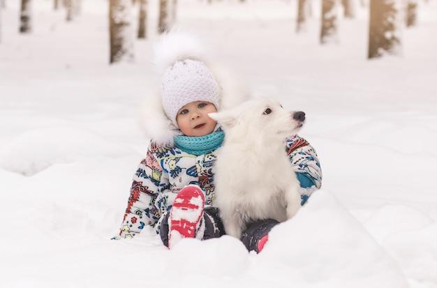 小さな女の子は白い小さな犬と一緒に雪の中で座っています。子供と動物の友情