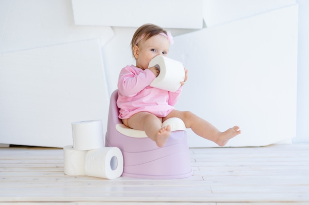 小さな女の子がトイレに座ってトイレットペーパーで遊ぶ