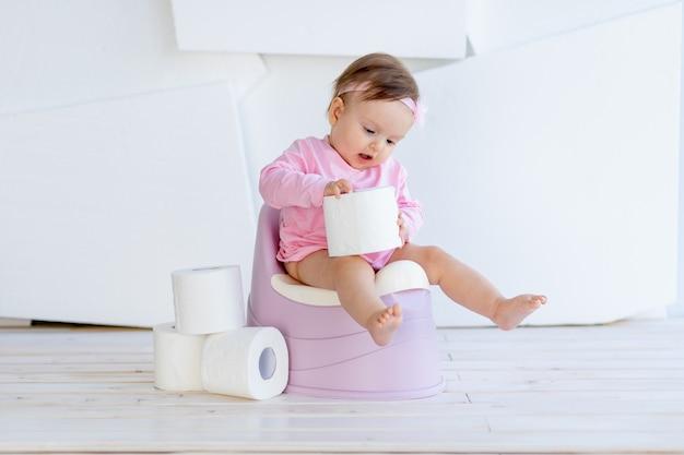 小さな女の子が明るい部屋でピンクの服を着たトイレに座ってトイレットペーパーで遊ぶ