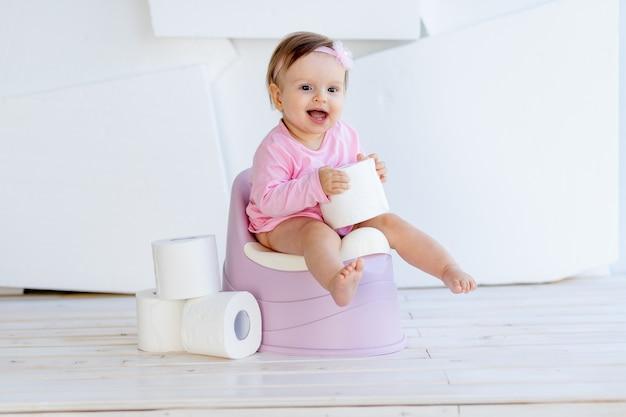 밝은 방에서 분홍색 옷을 입은 어린 소녀가 변기에 앉아 화장지를 가지고 노는