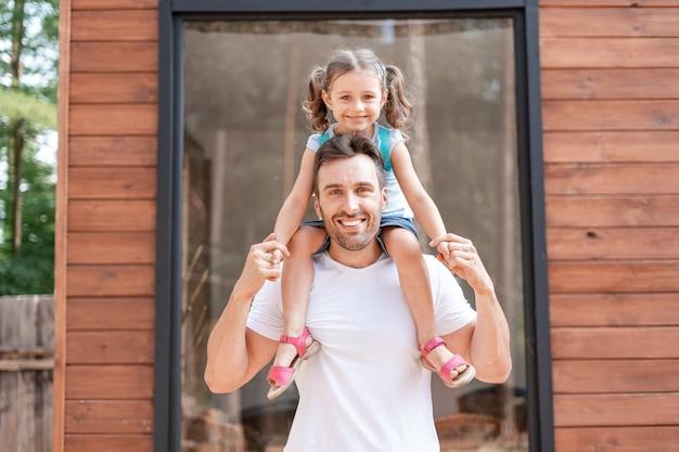 어린 소녀는 아빠의 어깨에 앉고 아빠는 소녀의 손을 잡고 여름 주말에 오두막 근처를 걷습니다