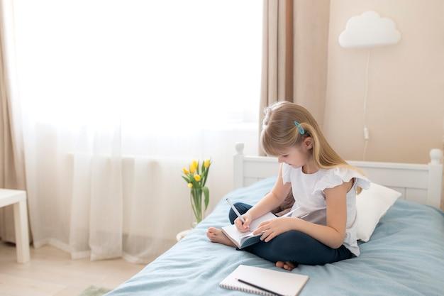 어린 소녀가 침실의 침대에 앉아 파란색 책에 글을 씁니다. 교육 개념. 홈 스쿨링. 숙제.
