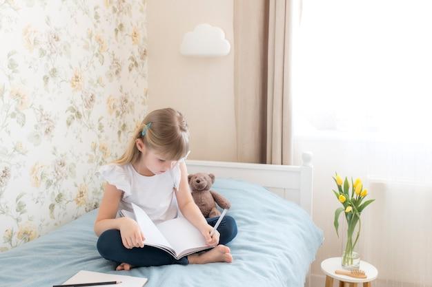 어린 소녀가 세련된 침실의 침대에 앉아 파란색 책에 글을 씁니다. 교육 개념. 홈 스쿨링. 숙제. 테이블에 노란 튤립