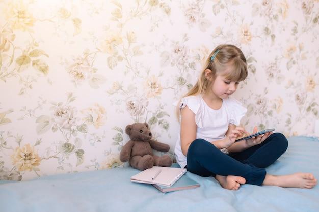 小さな女の子がスタイリッシュなベッドルームのベッドに座って、電話を持ってスマートフォンで何かを読みます。コミュニケーションの概念