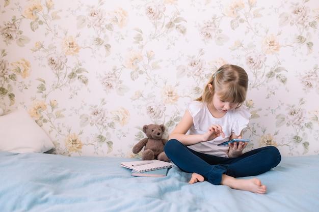 어린 소녀가 세련된 침실의 침대에 앉아 전화를 들고 스마트 폰으로 무언가를 읽습니다. 통신 개념