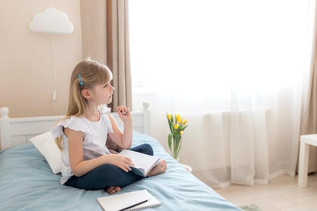 어린 소녀가 세련된 침실의 침대에 앉아 파란색 책과 펜을 들고 숙제를합니다. 문제 해결에 대해 생각합니다. 교육 및 가정 교육 개념. 숙제에 대한 생각