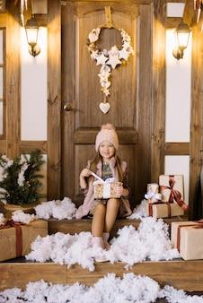 Маленькая девочка сидит на крыльце дома, украшенного на рождество и новый год. она держит в руках подарочную коробку, открывает ее лентой и улыбается