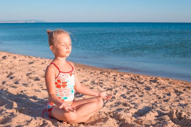 Маленькая девочка сидит на песке в позе лотоса и медитирует на занятиях йогой на берегу моря в
