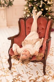 小さな女の子が椅子に逆さまに座っています。多動性の子供。