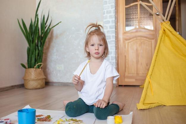 小さな女の子が床にブラシで座って、描く準備をします。子供の創造性