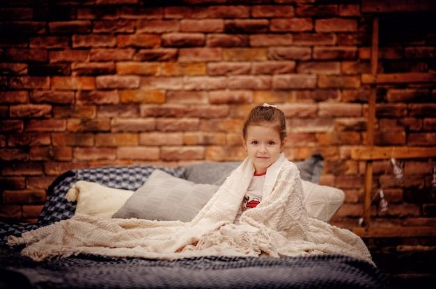 Маленькая девочка сидит на серой кровати, завернутая в белый плед, перед коричневой кирпичной стеной и смотрит в камеру. интерьер в стиле лофт. копировать пространство
