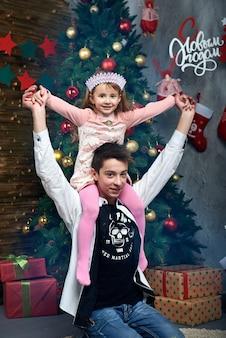 クリスマスツリーの近くの少年の首に座っている少女は、暖炉のそばで贈り物を受け取りました。