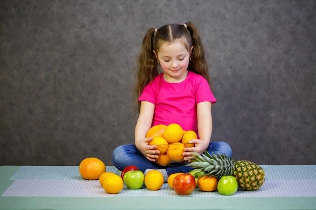 Маленькая девочка шести лет очень любит фрукты. витамины и здоровое питание.