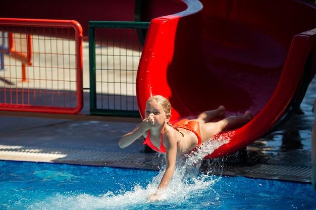 어린 소녀가 여름 방학 동안 워터 파크의 수영장으로 워터 슬라이드를 미끄러 져 내려갑니다.