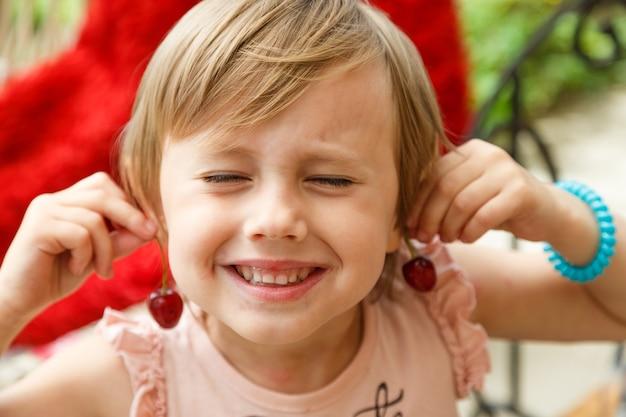Маленькая девочка улыбается и держит у ушей вишенки, словно сережки