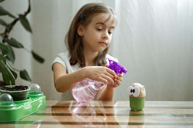 어린 소녀는 풀이 자라는 장난감 머리에 물을 뿌립니다.