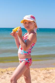 Маленькая девочка стоит у моря и ест кукурузу, летние каникулы и развлечения