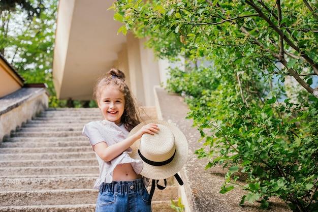 어린 소녀는 공원에 서서 손에 모자를 들고 있습니다. 아이는 행복하고 웃고 있습니다.