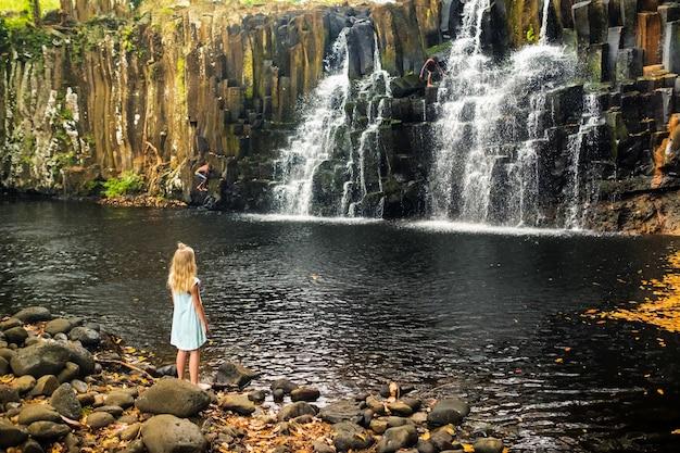 모리셔스 섬의 로체스터 폭포 근처에 서있는 어린 소녀. 열대 섬 모리셔스의 정글에있는 폭포.